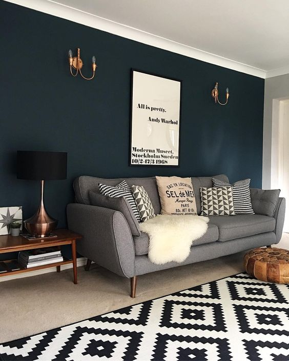 Dark blue wall color combined with gray sofa