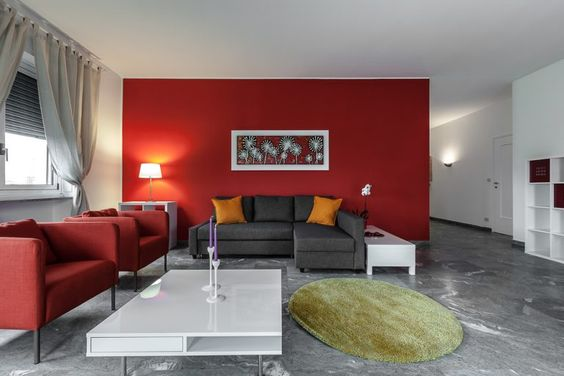 Red color on the wall combined with a gray sofa