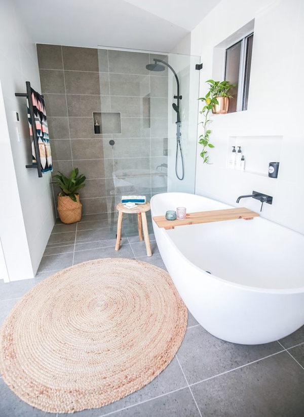 Bathroom in shades of gray and white with touches of wood and a round jute carpet