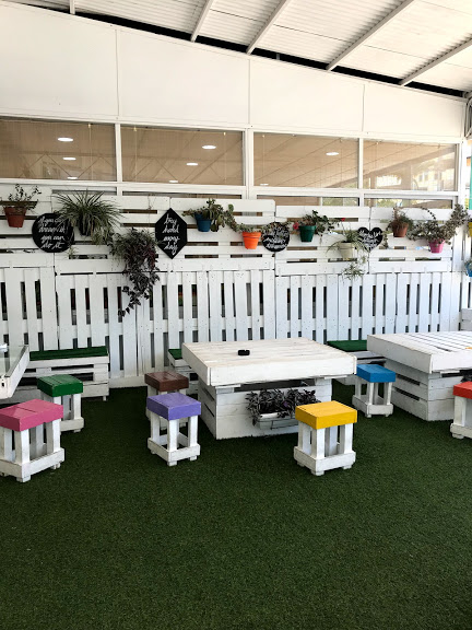 Terrace with artificial grass and furniture made of white painted wooden pallets
