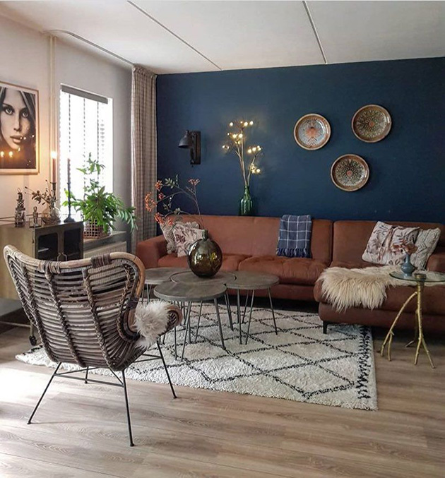A living room that combines navy blue on the walls and brown on the sofa