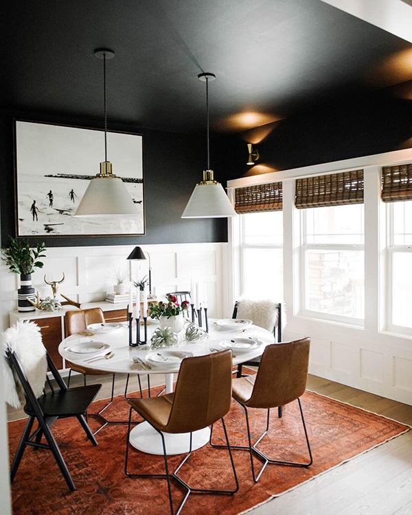 A dining room that combines black in the walls and ceiling and brown in the furniture