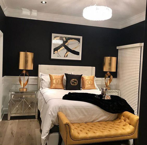 A bedroom that combines black on the walls with gold accents