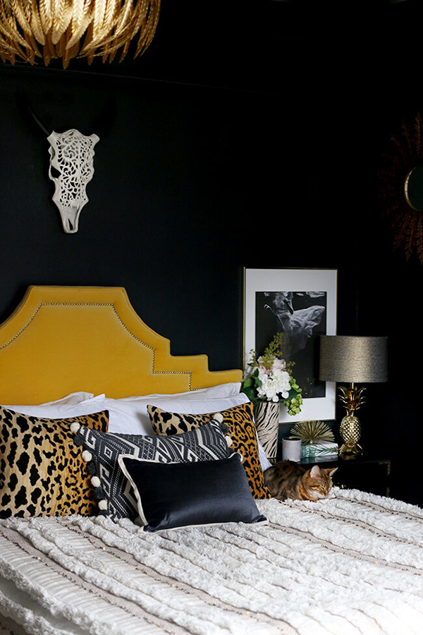 A bedroom that combines black on the walls and yellow on the headboard