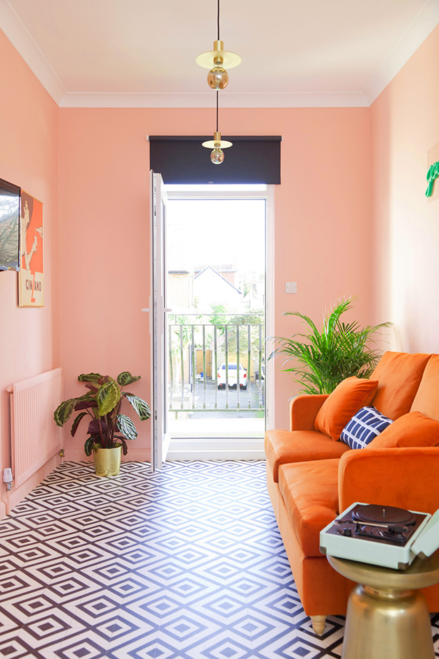 The living room is painted and decorated in pastel salmon colors