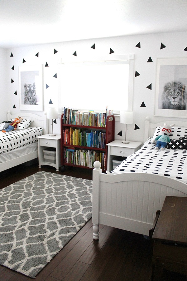 Shared children's bedroom with two black and white beds